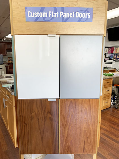 Examples of four kitchen cabinet doors made by local Hawaii cabinet makers. Grey, white, light and dark brown hardwood doors.