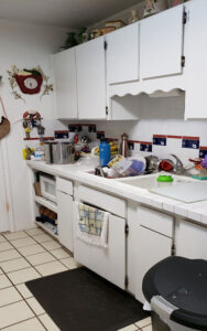 Picture shows part of a kitchen in Honolulu before undergoing renovation. Looks old, outdated, and crowded.